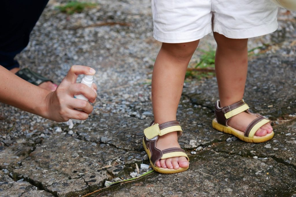 mom spraying repellent on a kid's leg