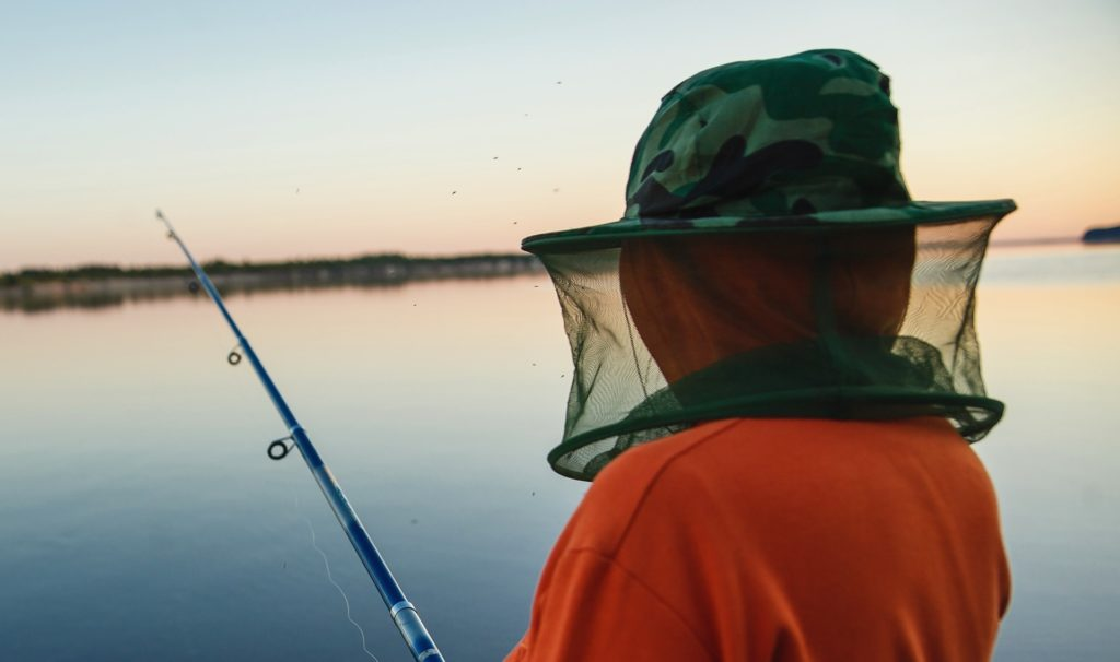 man fishing with a mosquito head net on