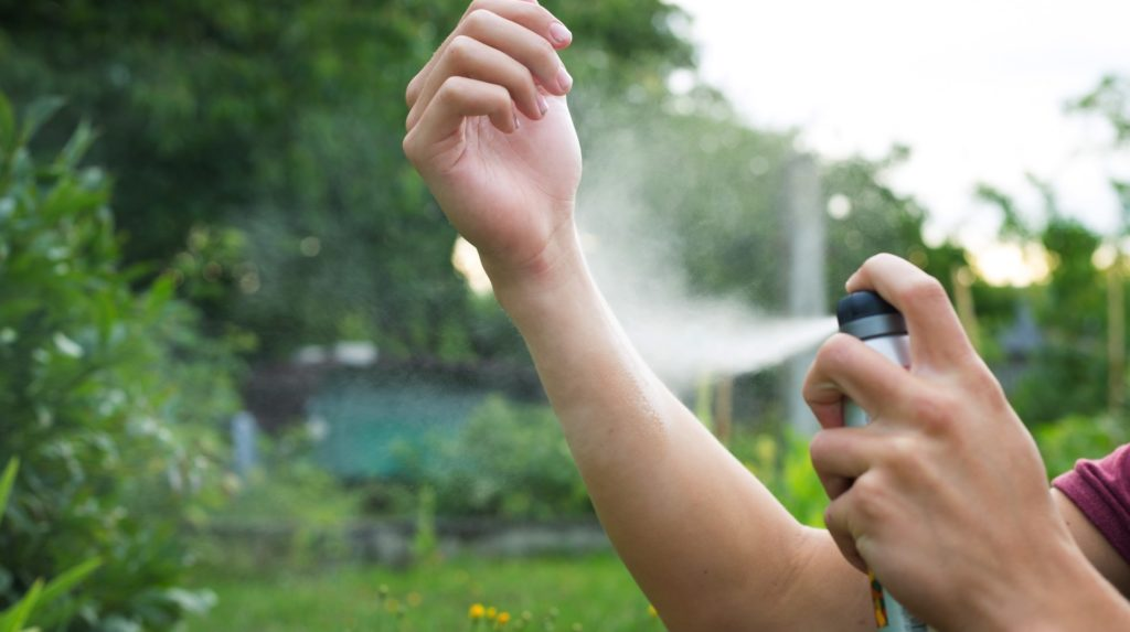 young man applying mosquito repellent on his arm